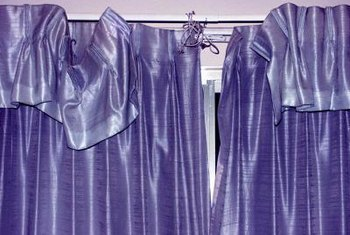 Pleated curtains hang from a rod using drapery pins.