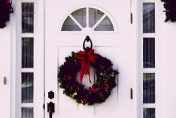 Tack a garland of greenery all around the front door to frame a wreath or a holiday poster.