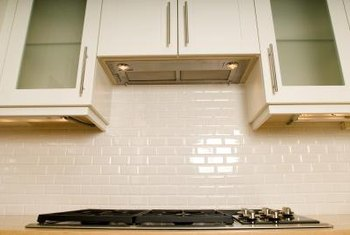Installing a subway tile backsplash is a budget-friendly way to update a '90s kitchen.