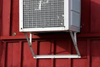 Ask an assistant to help you remove a wall-mounted air conditioner on the second floor.
