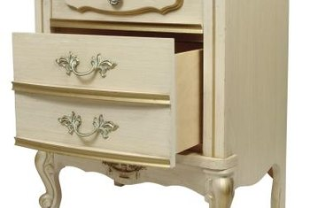 Gold trim accents a French Provincial nightstand.