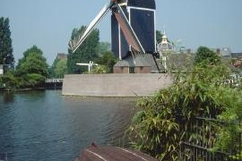 A windmill can take over a landscape near a water feature.