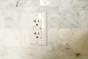 When finished, an electrical outlet should sit flush on the tile.