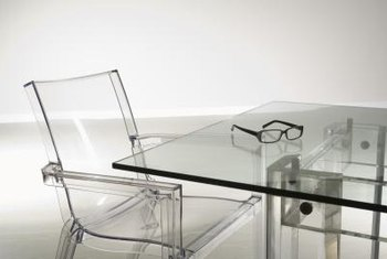 A Glass Table With Lucite Chairs And A Sleek Metal Base Nearly Disappears  In The Minimalist