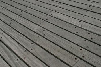 Sanding is preferable for removing finishes on a flat wooden deck.