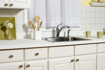 Fresh, white cabinets can be achieved through spray painting rather than replacement.