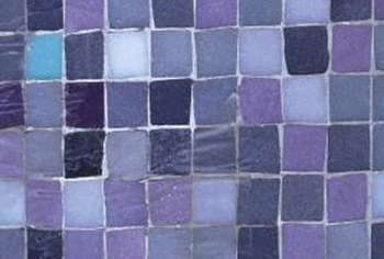 Fit the mosaic sheets around the outlet rather than trying to make a cutout in the sheet.