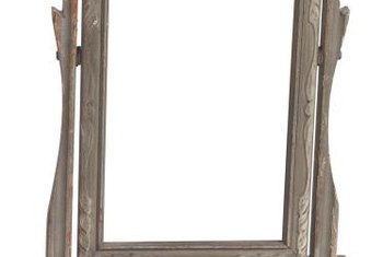 Use paint to add an aged look to wooden mirror frames.