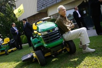 This mower, like the L120 model, features the familiar yellow-and-green color and John Deere logo.