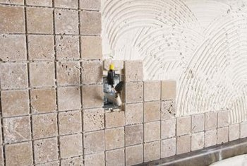 Both types of adhesive are applied to the backsplash in the same way.