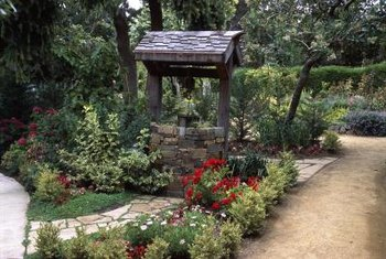 A natural stone path and a surrounding flower bed turn a wishing well into a peaceful garden retreat.