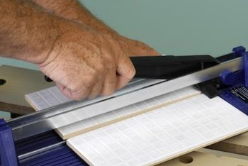 Cut tiles quickly using a tile cutter or by scoring and nipping.