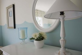 A well placed lamp, potted plant and candle frame a small round mirror attractively, eliminating empty space.
