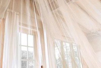 A hula hoop serves as support structure for a DIY bed canopy.