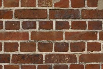 Softening construction adhesive is the best way to remove it from brick.