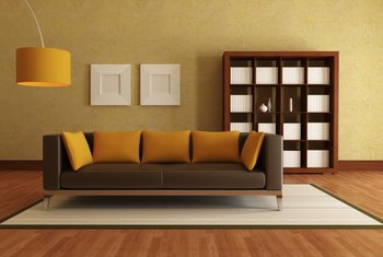 The orange, almost umber pillows and lampshade create a bridge between this muted yellow wall and brown sofa.