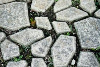 Weeds may grow in cracks between patio pavers placed directly on dirt.