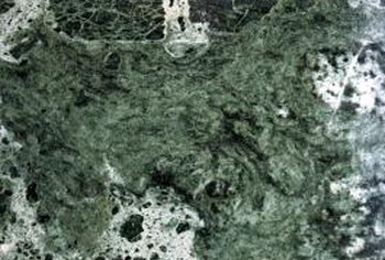 Green granite countertops can be a sophisticated complement to black cabinetry.