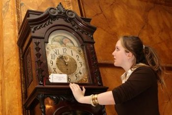 Custom-made grandfather clocks contain detailed molding and clock faces.