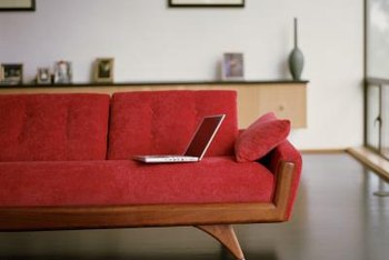 A red couch becomes the focal point in a room, highlighted by black floors.