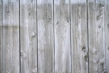 Use decorations to brighten a flat, gray, wooden fence.