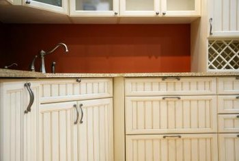 Update a country kitchen with vibrant walls and contemporary cupboard handles.