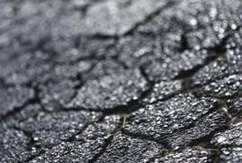 Pitting, weathering and cracking is a normal process for asphalt.