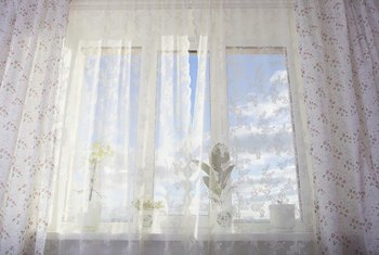 Hang curtains beyond the window's frame to make the window appear wider.