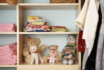 A wall of bookshelves in a small room holds neatly folded clothes, stuffed animals and books.