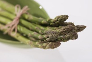 Add a pinch of baking soda to the water when you're boiling asparagus to keep them green.