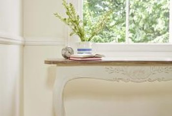 Placing a table under a window at the top of a staircase is a simple, classic decorating idea.