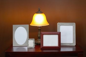 A taller lamp sets off a group of framed photos on a hall table.