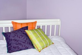 A pristine white bed and bold-colored toss pillows deliver visual contrast against purple walls.