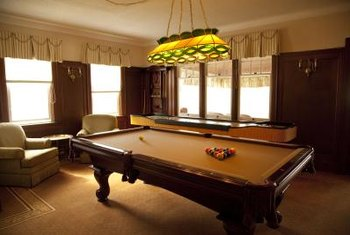 An elegant pool table and stained glass pendant are the focal point of this game room.