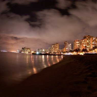 Oceanfront hotels in Waikiki offer the glamour of the city steps from gentle water.