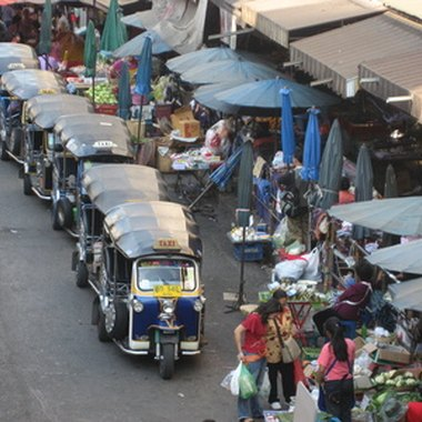 Tuk tuks, guttural sounding three-wheeled taxis, await passengers at one of Chiang Mai's many markets.