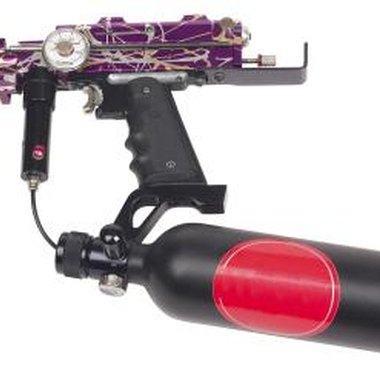 The HPA regulator attaches to the top of the CO2 tank and the paintball gun.