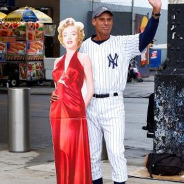 A man named Joe poses with a cutout of Marilyn Monroe before a New York Yankees game.