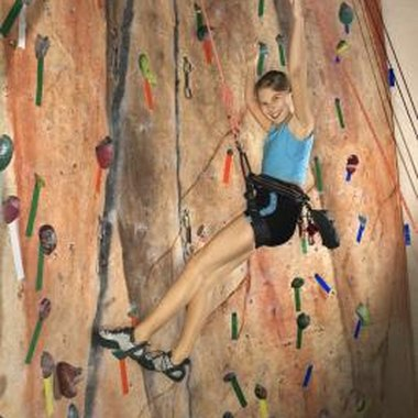 A teenage girl climbs an indoor rock climbing wall.
