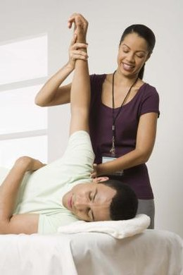 Physical therapy assistants may help a patient stretch his muscles to promote flexibility.