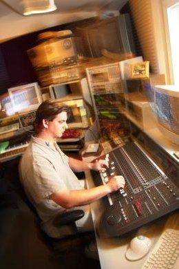An audio engineer puts his knowledge to work in a recording studio.