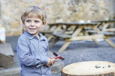Little boy playing with a hammer outdoors.