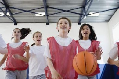 A group of students play basketball in a school gymnasium.
