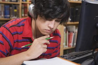 Student working on essay while in the library.