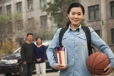 Smiling young college student holding basketball.