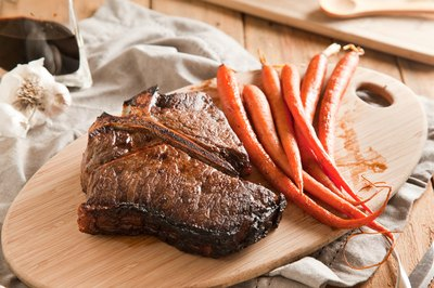 Cooked steak resting on a cutting with a side of cooked carrots.