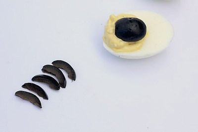 Black olives become the body and legs of the spiders.