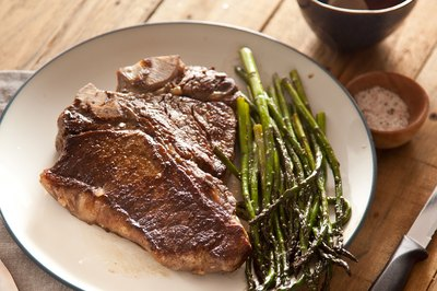 Grilled t-bone steak on white plate with a side of asparagus.