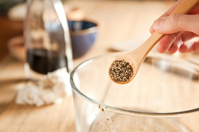Black pepper in a measuring spoon over a glass mixing bowl.