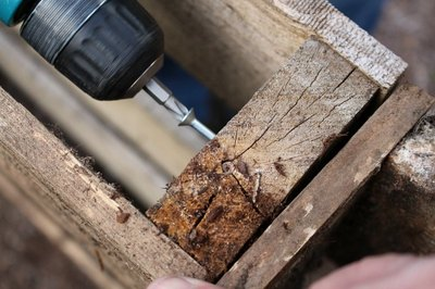 Drill the galvanized wood screws into the wood pallets.